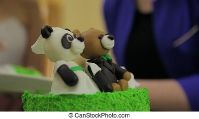 Panda or bear on green holiday cake. Birthday party with homemade torte for children. Bear cake.