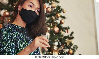 Pandemic fashion. Eastern beauty. Covid-19 festive look. Handmade accessory. Sad asian woman in mask drinking champagne