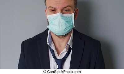 Pandemic protection of the Covid-19 coronavirus. Portrait of a tired caucasian man in a medical face mask. Concept impact of the pandemic - unemployment, poverty, disease