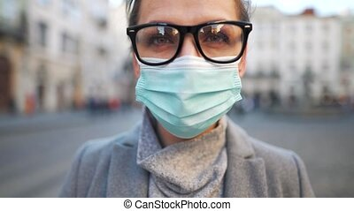 Pandemic protection of the Covid-19 coronavirus. Portrait of a woman in a coat, glasses and a protective medical mask. Glasses fog up from breath. Virus protection. Slow motion