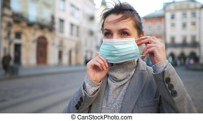 Pandemic protection of the Covid-19 coronavirus. Woman in a coat stands in the middle of the square, puts on a protective medical mask. Virus protection.