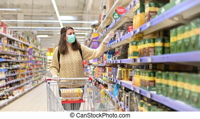 Young beautiful woman at shopping in hypermarket, wearing a medical face mask, during pandemic