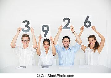 Panel judges holding score signs - Portrait of panel judges...