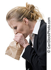 panic attack - woman breathing into a brown paper bag
