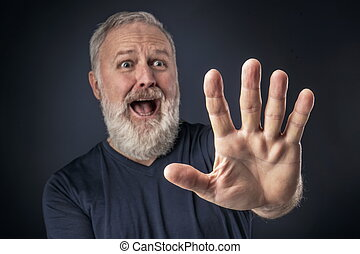 Panicked old man with his stretched hand forward