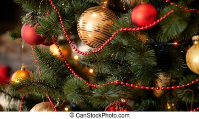 Paning 4k footage of camera moving along beautiful decorated christmas tree with colorful babubles and lights