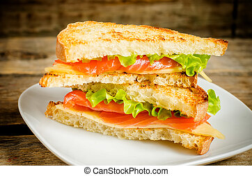 panini sandwiches with salmon, cheese and salad on a dark wood background. toning.