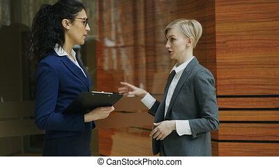 Paninning shot of two businesswomen talking in modern office...