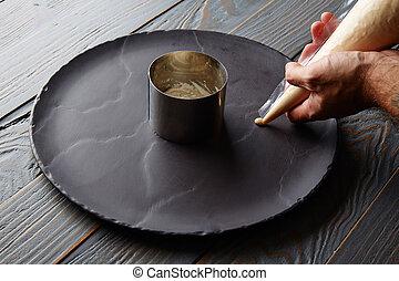 pannacotta preparation with chef hands on black slate dish