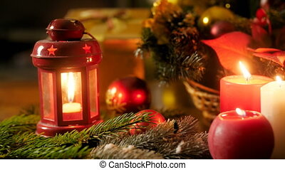 Panning 4k video of burning candles, lanterns and Christmas wreath lying on table. Perfect background for winter celebrations and holidays
