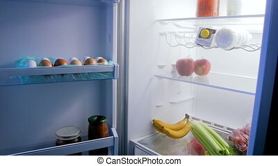 Panning footage of open refrigerator full of food at night
