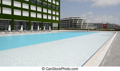 Panning left of building and swimming pool at the modern...