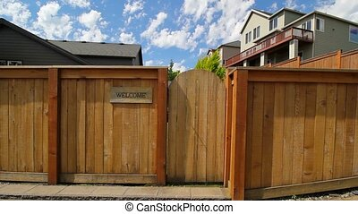 Panning movie of wood fence with entrance gate to garden an welcome sign 1080p hd