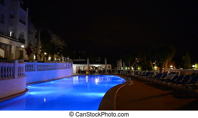 Panning of swimming pool at the luxury hotel in night...