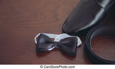 Panning shot of all the groom's clothes: shoes,belt,cuff links,tie