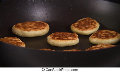 Panning shot of big pikelets being cooked in a saucepan on a...