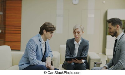 Panning shot of businesswoman with digital tablet duscussing with male business colleagues sitting on couch in modern office