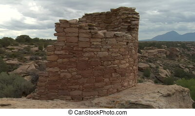 panning shot of ruins at Hovenweep national Monument with mountains in distance