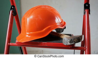 Panning shot of working tools and red hardhat lying on...