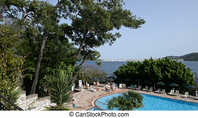 Panning the swimming pool and view on yachts harbor,...