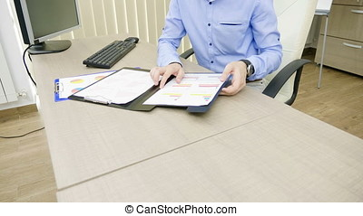 Panning up on Ambitious young businessman is working in his office at the computer next to folders filled with charts