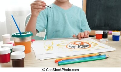 Panning video of little boy prawing picture with colorful paint on white paper at domestic classroom. Creative child doing art painting. Education at home during lockdown.