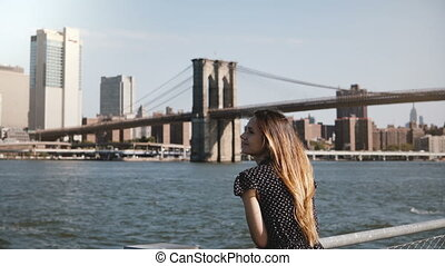Panning view of happy smiling European woman with flying hair enjoying famous New York skyline and Brooklyn Bridge view.