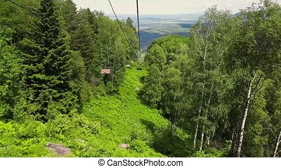 Panorama aerial view on ropeway. Chairlift in forest....