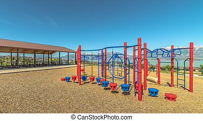 Panorama Climbing bars and steps playground equipment at a park against lake and mountain