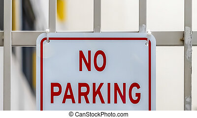 Panorama Close up of No Parking sign on awhite metal gate with building in the background