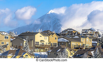 Panorama crop Homes on frosted neighborhood setting with view of snowy Wasatch Mountains