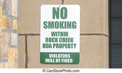 Panorama crop No Smoking sign on the exterior stone wall of apartment in Rock Creek Utah
