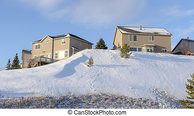 Panorama crop Wasatch Mountains on a sunny winter day with mountain homes against blue sky