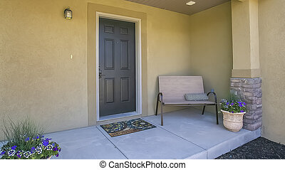 Panorama Entrance of a home with bench and potted flowering plants on the porch
