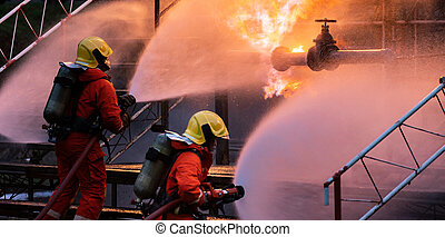 Panorama Firefighter team using water fog spraying down fire from oil rig factory explosion