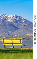 Panorama frame Empty bench facing an amazing view of a lake and mountain capped with snow