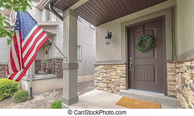 Panorama frame Front door of suburban home with American flag