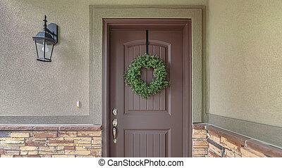 Panorama frame Front door of suburban home with green wreath