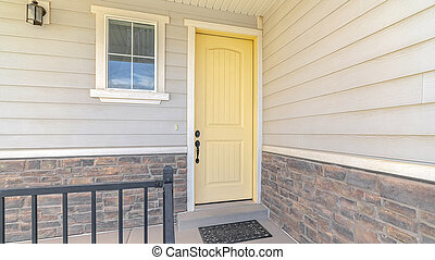 Panorama frame Front porch of suburban home with a yellow door
