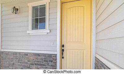 Panorama frame Front veranda of suburban home with a yellow door