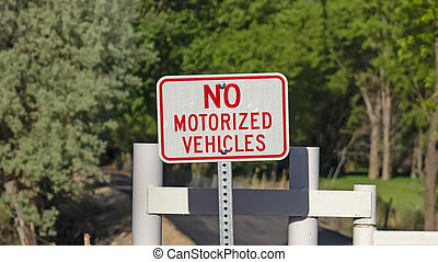 Panorama frame No Motorized Vehicle sign against a white gate and narrow road on a sunny day