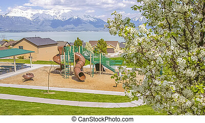 Panorama frame Playground and residential area against lake and mountain under cloudy blue sky