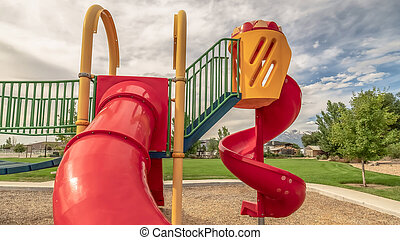 Panorama frame Red closed tube slide and spiral slide at a playground against cloudy blue sky