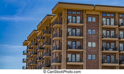 Panorama frame Residential brick building with balconies against blue sky with thin clouds