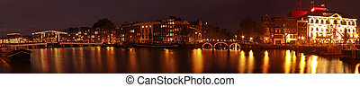 Panorama from Amsterdam at night at the Amstel with the Thiny Bridge in the Netherlands