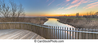 Panorama from wooden balustrade over swamp at sunset