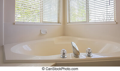 Panorama Gleaming heart shaped built in bathtub at the corner of a bathroom