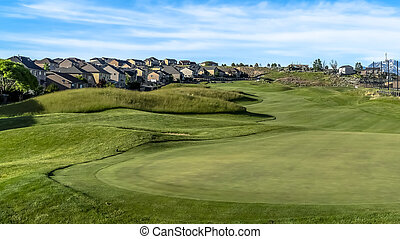 Panorama Golf course and homes under blue sky with clouds viewed on a sunny day
