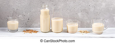Panorama image of row of glass containers with oat milk on white wooden table on grey concrete wall background.