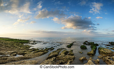 Panorama landscape looking out to sea with rocky coastline and b